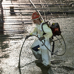 Experienced concrete worker uses a vibrating tool during an early morning concretepour with smoothing and shaping on the top floors of a high-rise parking garage in downtown Austin on Augut 22, 2020. Major construction projects continue unabated during the coronavirus shutdowns in Texas.