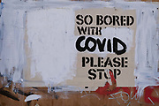 An altered message on the outside of a closed business on Charing Cross Road, stating the writers boredom with Covid restrictions, during the third lockdown of the Coronavirus pandemic, on 30th March 2021, in London, England.
