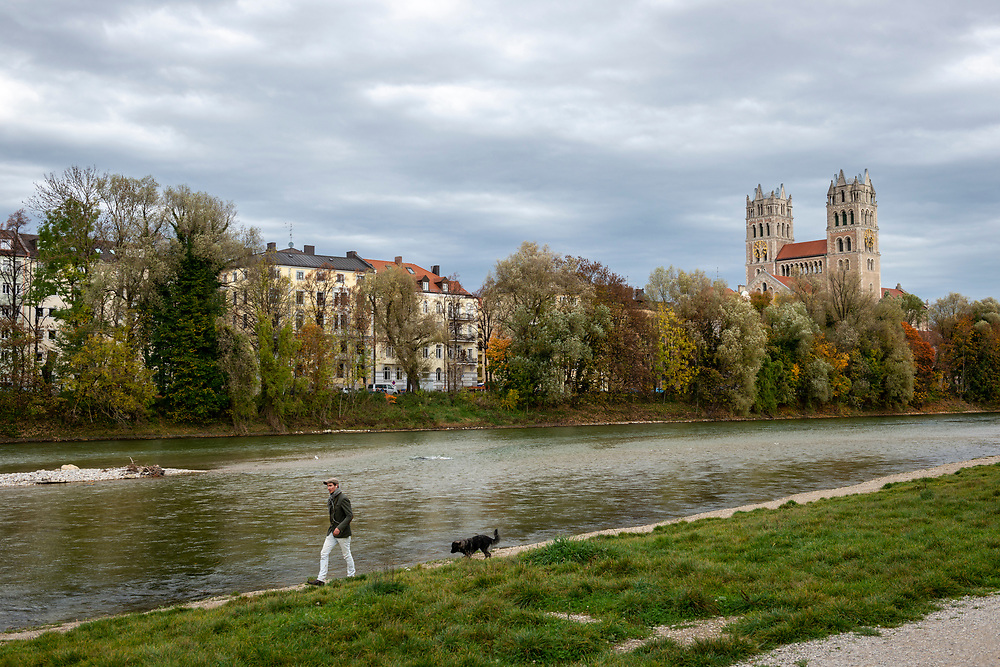 Munich, Germany - October 27, 2013: A man and dog walk beside the Isar River on an autumn afternoon in Munich, Germany. St. Maximilian, a Roman Catholic parish church built from 1892 to 1908 in the Romanesque Revival style, is across the river.