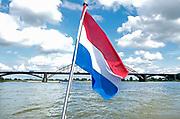 Nederland, Nijmegen, 20-7-2017Nederlandse vlag wappert op een boot die over de Waal, Rijn vaart. Op de achtergrond de oude Waalbrug.Foto: Flip Franssen