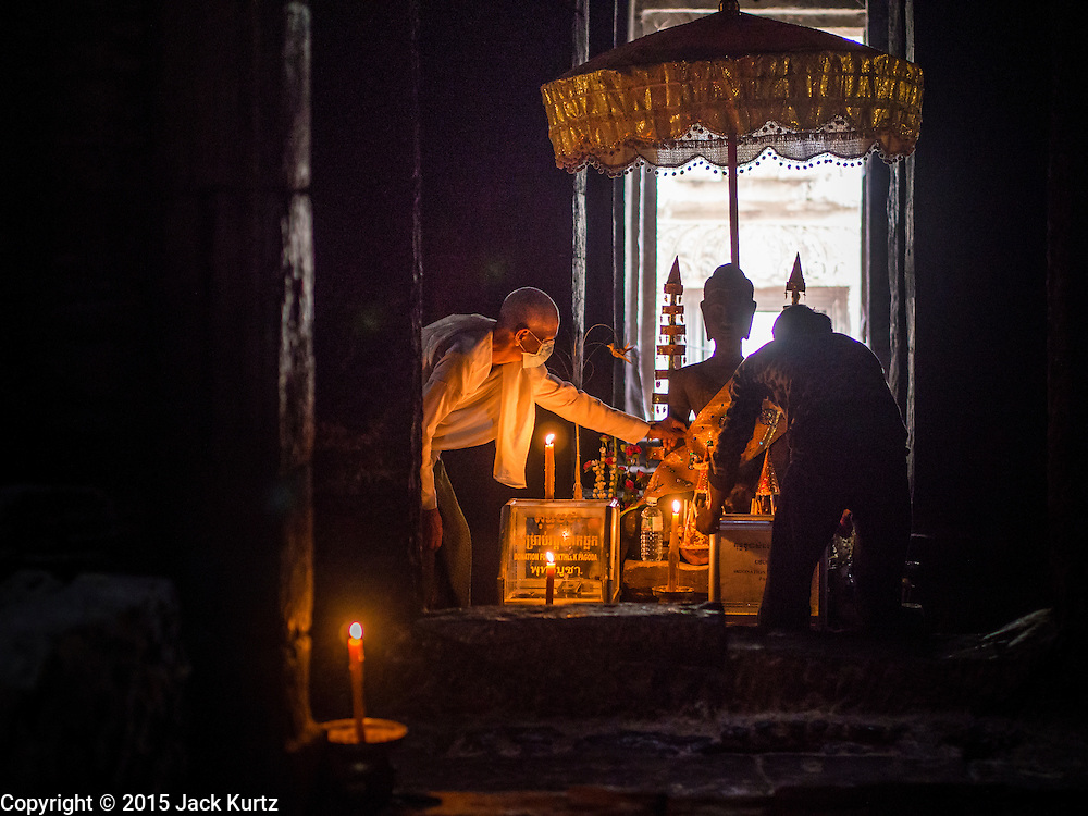 """14 MARCH 2105 - SIEM REAP, SIEM REAP, CAMBODIA: A Buddhist lay woman sets up a prayer room in Bayon, one of the temples in Angkor Thom, a part of the Angkor Wat complex. Bayon was built in 12th or 13th century CE. The area known as """"Angkor Wat"""" is a sprawling collection of archeological ruins and temples. The area was developed by ancient Khmer (Cambodian) Kings starting as early as 1150 CE and renovated and expanded around 1180CE by Jayavarman VII. Angkor Wat is now considered the seventh wonder of the world and is Cambodia's most important tourist attraction.   PHOTO BY JACK KURTZ"""