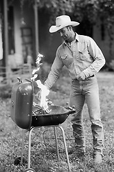 Cowboy by a lighted barbeque