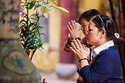 05 APRIL 2012 - HANOI, VIETNAM:   Women pray in the Bach Ma (White Horse) temple in Hanoi, the capital of Vietnam. The Bach Ma temple honors a white horse which was thought to be an incarnation of a local river god. In the spring of the year 1010, the founder of the Ly dynasty, Ly Thai To transfered the capital of Vietnam to today's Hanoi. Ly established Bach Ma temple in 1010 to honor the White Horse who, according to local mythology helped him fortify the city. The temple has been damaged by flooding and other natural disasters over the course of the past thousand years. The present buildings date from the 18th and 19th centuries.  PHOTO BY JACK KURTZ