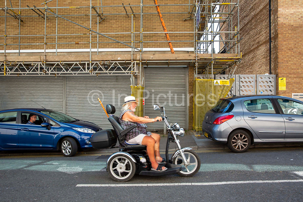 An elderly man dressed in shorts and a vest cruises up the road on his Harley Davidson style mobility scooter on his way to Folkestone Town Centre on the 15th of June, in Folkestone, United Kingdom.