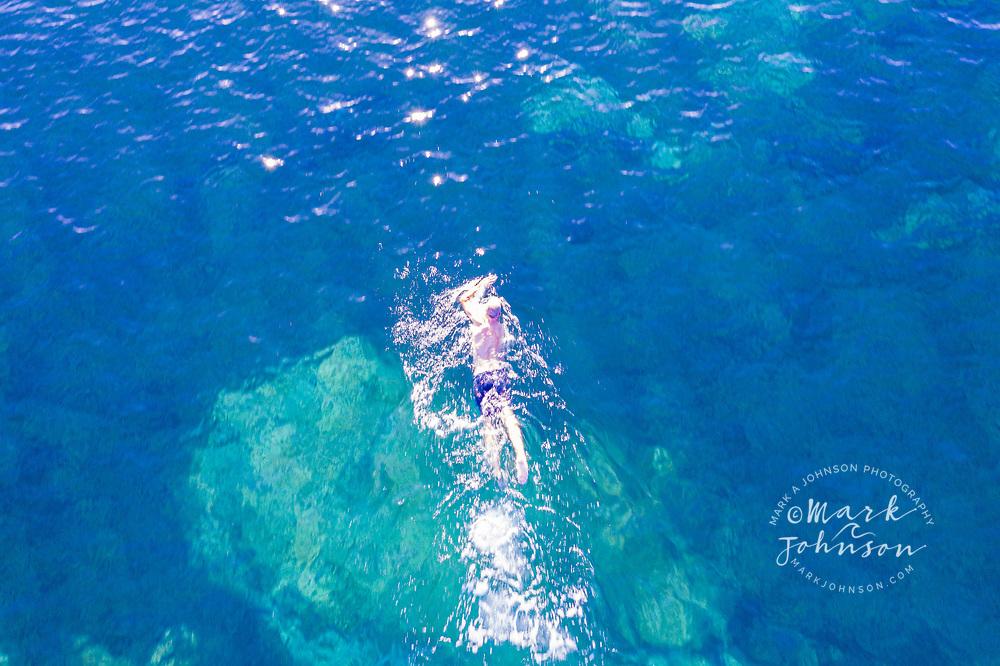 Aerial view of man swimming off of Shelly Beach, Caloundra, Sunshine Coast, Queensland, Australia