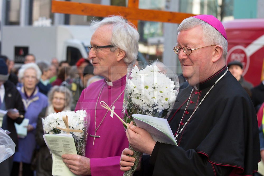 © Licensed to London News Pictures. 25/3/2016. Birmingham, UK. Good Friday Walk of Witness. Churches in Birmingham come together to walk through Birmingham City Centre, visiting Cathedrals and Churches.<br /> Pictured, Bishop David Urquhart and Archbishop Bernard Longley (right) receive flowers from local shopkeepers on New Street. Photo credit : Dave Warren/LNP