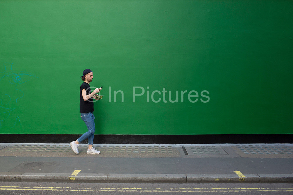 Street Scene of people passing by a green painted wall on in Soho, London, England, United Kingdom. The simplicity of the scene helps highlight the figures of ordinary people going about their daily lives. Man texting and carrying his lunch.