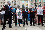 A group of Extinction Rebellion activists dressed face masks and blue suits hold up placards, with one holding a bloodied globe on 27th August, 2021 in London, United Kingdom. The activist group Extinction Rebellion XR are planning actions of disruption for two weeks straight beginning on August 23rd, 2021 in an effort to bring awareness and priority to the global climate emergency in advance of the COP 26 Summit which will be held in Glasgow later this year.
