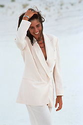 woman in a white suit , smiling while walking through white sands, New Mexico