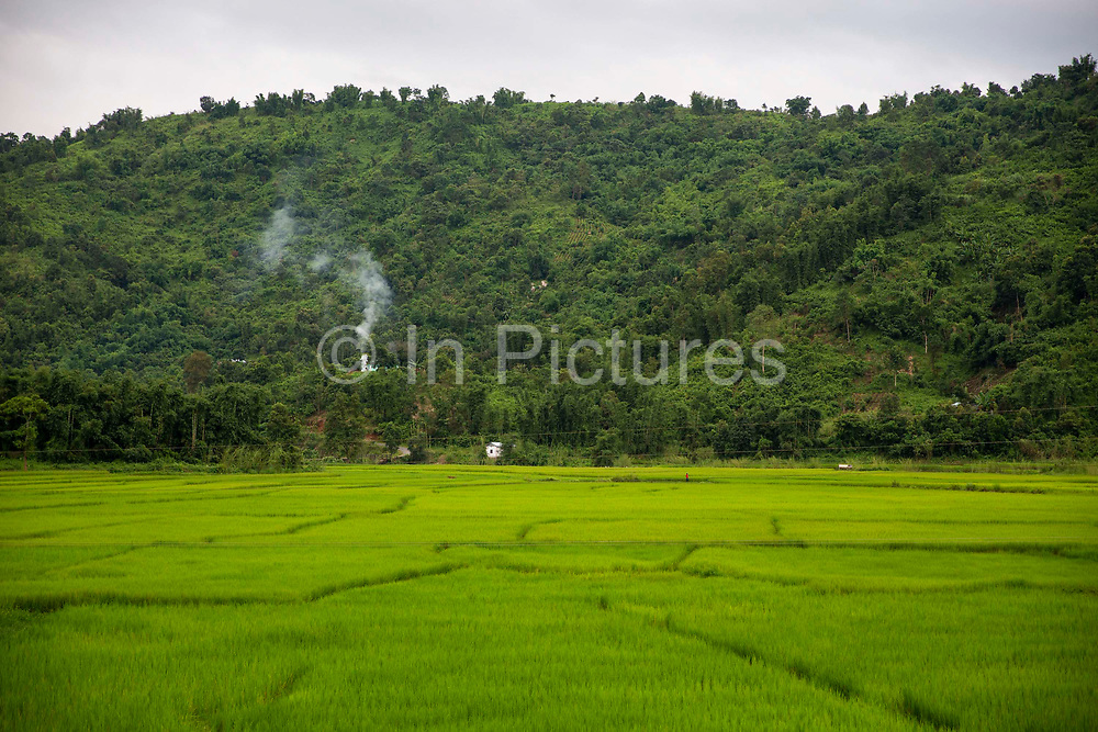 Smoke billows out from a building hidden in the side of a wooded hill above a large paddy field near Nongpoh, Ri-Bhoi district on 20th September 2018 in Meghalaya, India.