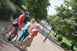 Cyclist talking to two older women,