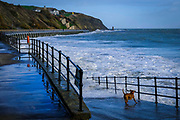 A brown dog chases the waves crashing over the walkway down to Sunny Sunny Sands Beach on 8th December 2018 in Folkestone, Kent, United Kingdom. The tide is high covering all the beach and the sea is rough from stormy weather.