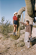 CS03613 Photographer with a Speed Graphic camera directing a model perched on a cactus in the American Southwest. Kodachrome, mount dates ca. 1955 to 1957