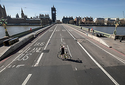 FILE IMAGE © Licensed to London News Pictures. 24/03/2020. London, UK. A cyclist stops in the middle of an almost deserted Westminster Bridge to take a phone photograph at 1:15pm  after Prime Minister Boris Johnson announced that the UK will now lockdown in order to fight the spread of the coronavirus. Only essential journeys for food and one period of excercise will be allowed per day. Photo credit: Peter Macdiarmid/LNP