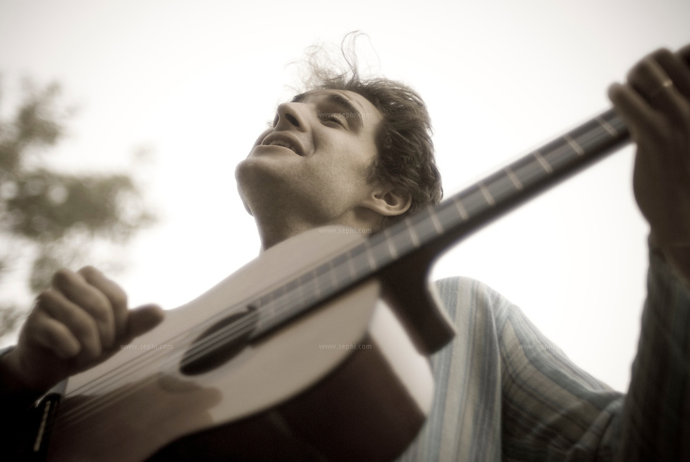 a young french guy playing his guitar on a sunday afternnon in New Delhi