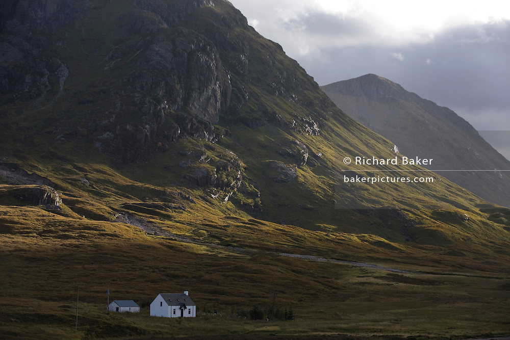 A crofter's cottage sits isolated at the foot of a dramatic craggy valley at Altnafeadh in Glencoe, Scottish Highland Mountains