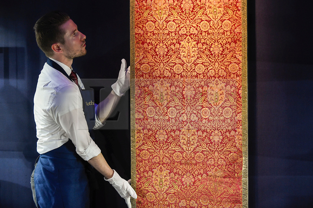 """© Licensed to London News Pictures. 18/10/2019. LONDON, UK. A technician presents a """"A rare and important Ottoman silk and metal-thread brocade panel (Kemha)"""", Turkey, probably Bursa, early 17th century (Est. GBP60,000-80,000).  Preview of Islamic, Indian and Middle Eastern art to be auctioned at Sotheby's, New Bond Street, on 22 and 23 October.  Photo credit: Stephen Chung/LNP"""
