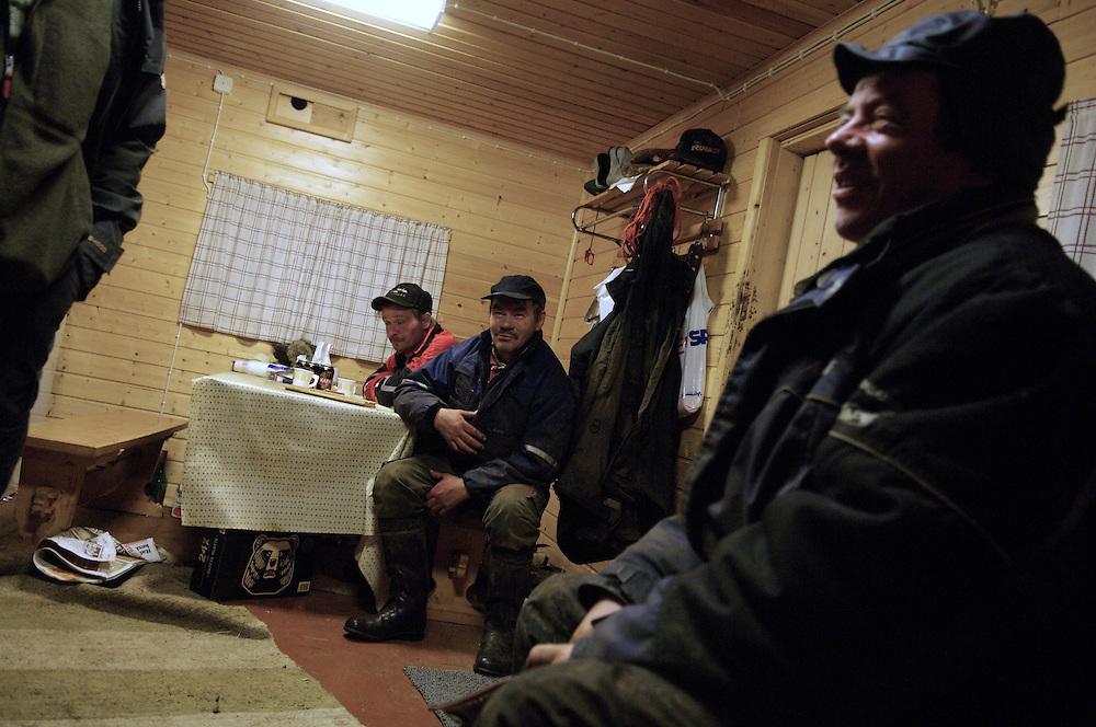 Hirvas Salmi, FINLAND. October 18, 2007- Veggai, 58, (far right) and friend Pauli (center) share beers, unwinding after a long day.