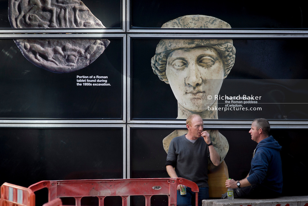 City workers take a break below the Roman archaeology showing the Goddess Minerva on Walbrook, City of London, founded by the Romans in AD43.