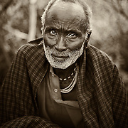 """""""Old...Wise...Gentle""""                                         Tanzania<br />   While watching the young men of the Datoga tribe making bracelets and arrowheads for trade, this Datoga elder quietly came and crouched by the fire.  He had a presence about him. It was one of age, a gentle wisdom gained over the years.  Watching the passing of his knowledge to those young men hammering the red-hot metal into the items to trade. You can see the years in his eyes, and the stories of lions in the night, and the tenderness he shared with his children."""