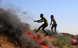 June 16, 2017 - Gaza City, Gaza Strip, Palestinian Territory - A Palestinian protester uses a slingshot to hurl stones towards Israeli security forces during clashes following a demonstration against the blockade on the Gaza Strip, near the border fence east of Jabalia refugee camp on June 16, 2017  (Credit Image: © Yasser Qudih/APA Images via ZUMA Wire)