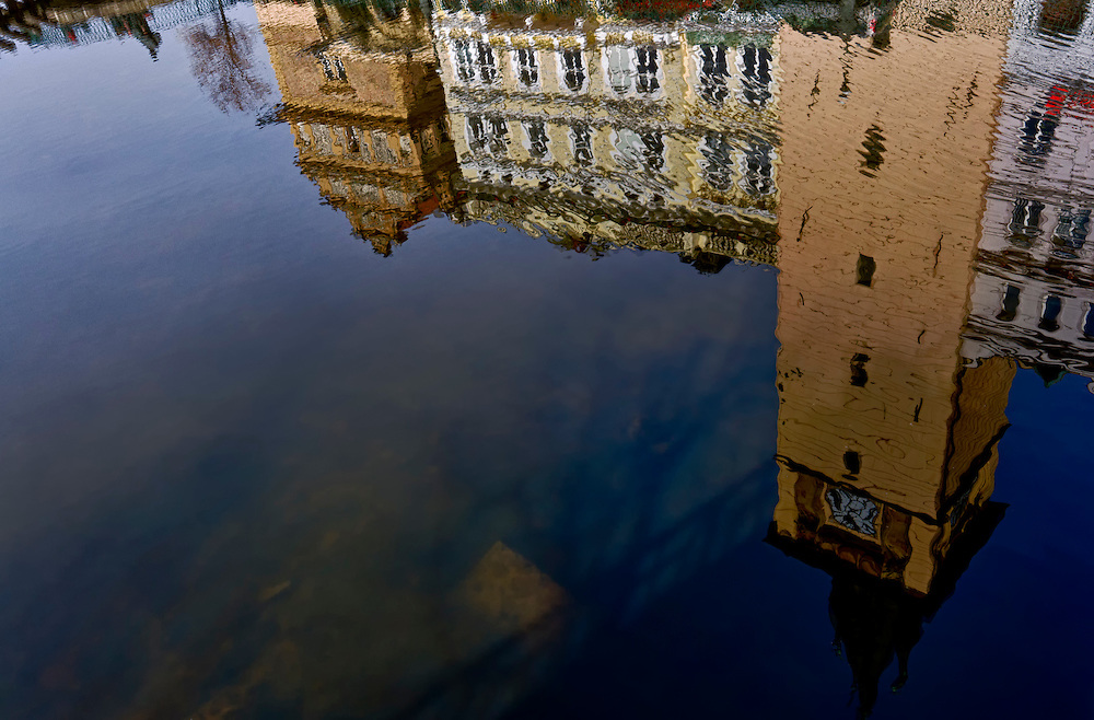Historic buildings in Prague reflecting over the Vltava river.