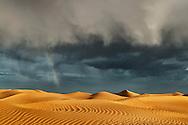 Sahara sand dunes with stormy, cloudy sky and rainbow at Erg Lihoudi, M'hamid, Morocco.