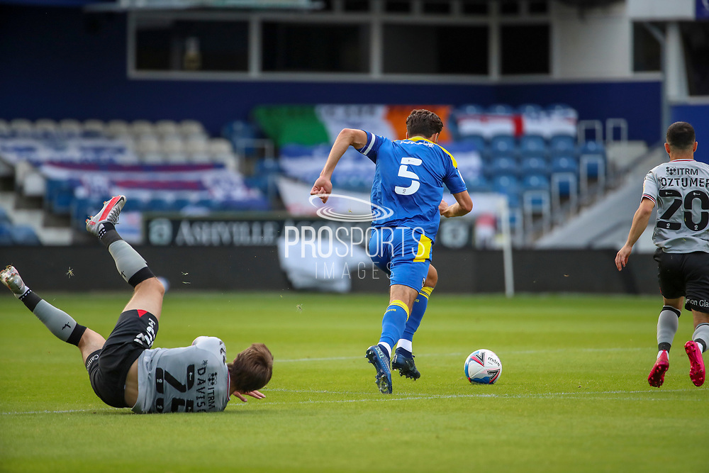 AFC Wimbledon defender Will Nightingale (5) tackling Charlton Athletic attacker Nicky Ajose (25) with Charlton Athletic attacker Nicky Ajose (25) on the floor  during the EFL Trophy Group O match between AFC Wimbledon and Charlton Athletic at the Kiyan Prince Foundation Stadium, London, England on 1 September 2020.