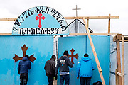 France. Refugees. Calais. So-called Jungle camp . Young men about to enter the Ethiopian/Eritrean church, St Michael's.