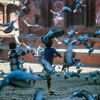 Youngsters chase pigeons between temples at Durbar Square,  Kathmandu, Nepal, 1986.