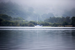 © Licensed to London News Pictures. 14/09/2016. Glenridding UK. Picture shows a boat on the still water of Ullswater Lake in the morning mist at Glenridding this morning. After last nights thunderstorms in the north of England Cumbria woke to a calm but misty morning. Photo credit: Andrew McCaren/LNP