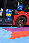 A Covid pandemic face mask sign is on the side of a London bus as it passes over the multi-coloured markings of a crossing at Lower Regent Street, on 16th July 2021, in London, England. Days before the UK government's widespread re-opening of Covid pandamic restrictions (Monday 19th July aka Freedom Day), the number of daily infections has risen to 50,000.