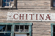 "Painted sign for ""Chitina"" on an old, wooden storefront in Chitina, Alaska."