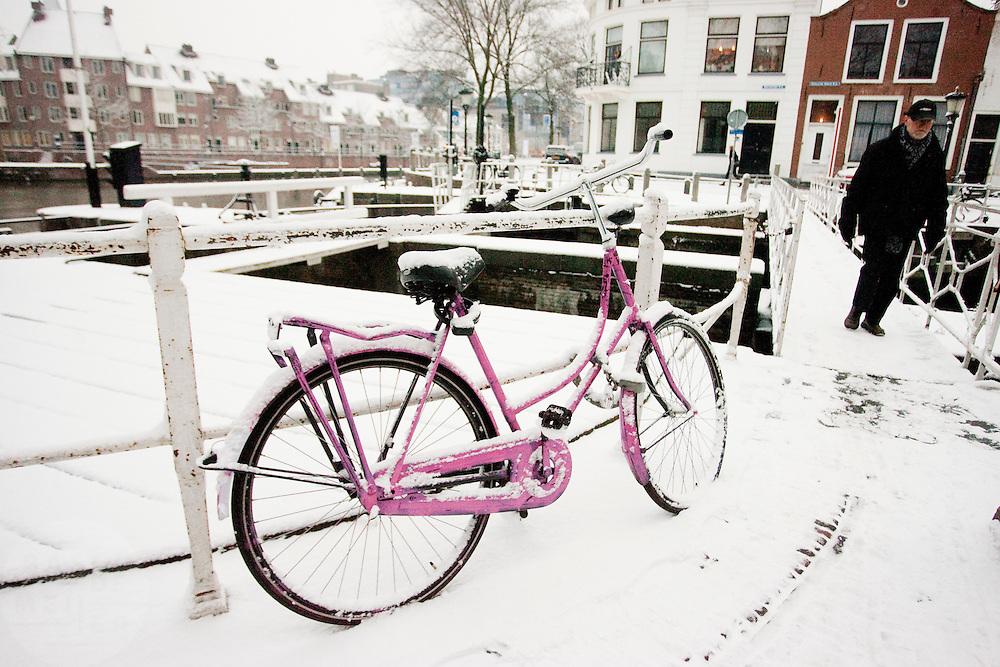 Een man loopt over een bruggetje door de sneeuw in Utrecht. In grote delen van Nederland is vandaag voor het eerst sneeuw gevallen