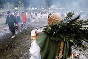 A Yamabushi or Mountain priest in green robes watches japanese people walk across the hot coals of a large bonfire during the Hi Watari fire walking festival in Takao san Guchi, near Tokyo, Japan. Sunday March 11th 2007