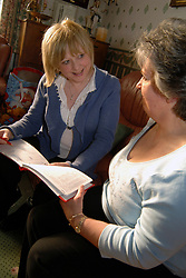 Health visitor talking to foster carer in her home; Bradford; Yorkshire UK