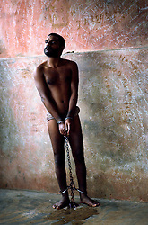 Tamil Nadu, INDIA. March1994..A man who has his hands and feet chained is standing upright looking obliviously in the distance. .This is the fate awaiting those, who the locals believe are possessed by evil spirits.