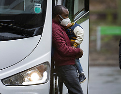 © Licensed to London News Pictures. 16/02/2021. London, UK. A passenger carries his child on arrival for quarantine at a Holiday Inn hotel near Heathrow Airport for the second day. People entering the UK from a 'red list' of 33 high risk countries will have to quarantine at hotels for 10 days to try and stop new coronavirus variants entering the country. Photo credit: Peter Macdiarmid/LNP