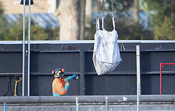 © Licensed to London News Pictures. 14/12/2019. London, UK. A bag containing the remains of a WW2 bomb are lifted from the Thames Tideway sewer works building site at Chelsea Embankment next to The River Thames after a controlled explosion was carried out. Photo credit: Peter Macdiarmid/LNP