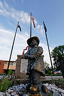 A firefighter statue in a memorial at a firehouse with blue skies and flags in the background