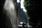 Een man reinigt een gevel van een oud pand met een hogedrukspuit
