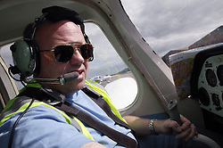 Man with disability; who is wheelchair user; sitting in aircraft cockpit; wearing earphones and mouthpiece; preparing to fly plane,