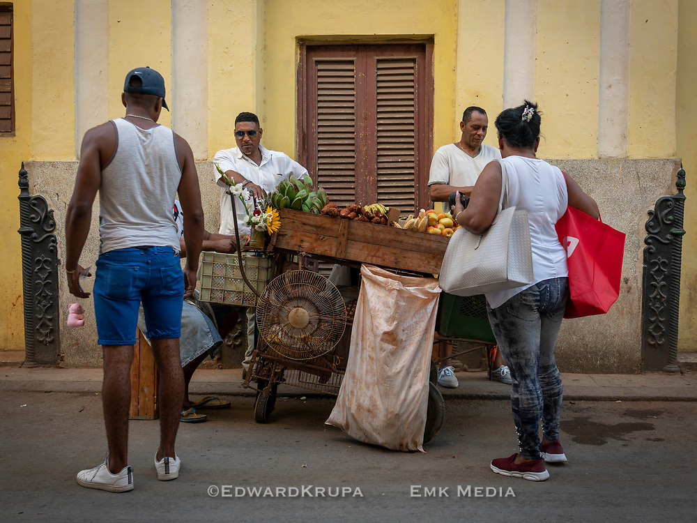 People gathered around a fruit and vegetable cart in Havana.