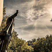 A plane heads in to land at the nearby Reagan National Airport, while the sun casts a sharp shadow on the stone backdrop at the Theodore Roosevelt Memorial in Arlington, Virginia, just across the Potomac from the National Mall and Georgetown in Washington DC.