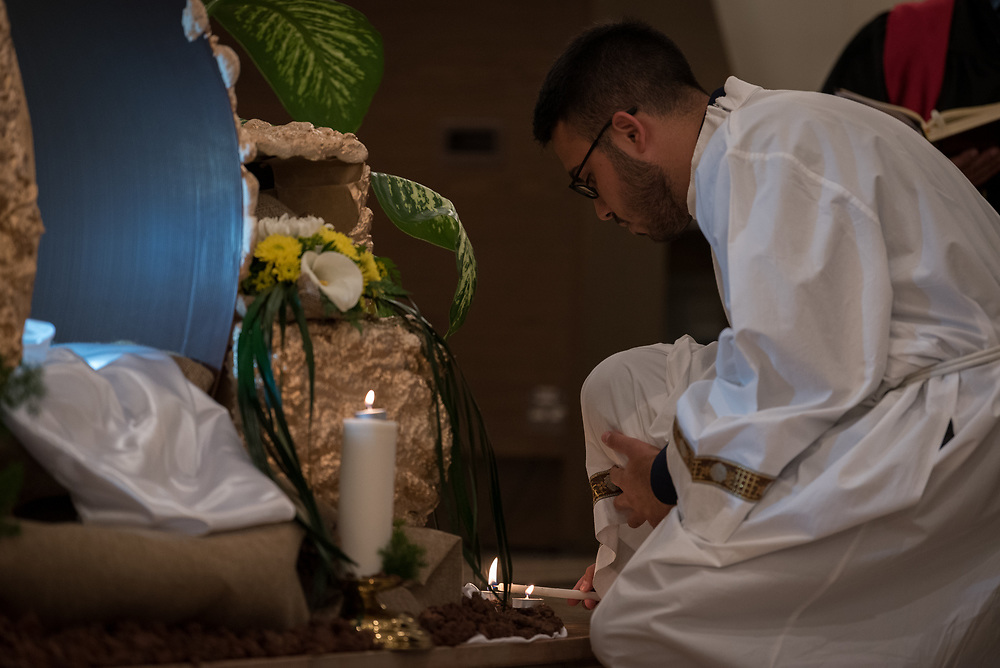 20 April 2019, Jerusalem: A man lights candles by the grave during Holy Saturday service at Saint James' Church in Beit Hanina, Jerusalem.