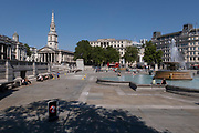 Trafalgar Square remains incredibly quiet apart from a few people keeping cool by sitting near the fountains during high summer temperatures under Coronavirus lockdown on 25th June 2020 in London, England, United Kingdom. As the July deadline approaces and government will relax its lockdown rules further, the West End remains quiet, while some non-essential shops are allowed to open with individual shops setting up social distancing systems.