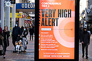 People pass a very high alert level warning sign while out and about visiting the shops in the City Centre as tier three / very high alert level of the Coronavirus tier system continues during the run up to Christmas on 14th December 2020 in Birmingham, United Kingdom. After 9 months of lockdown in various forms, people are used to navigating the rules of shopping safely as all non-essential shops try to increase their takings and onwards to the national economy.