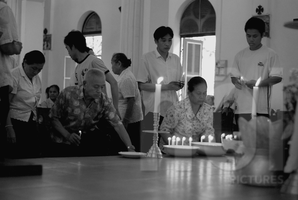 A group of worshipers light candles in a church of Vientiane, Laos, Asia