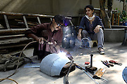 Naiza Khan working in her garden with Mohammad kasim who welds together her sculptures.
