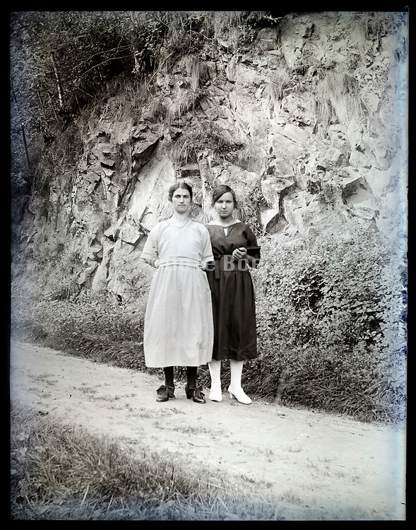 two adult women on small rural countryside road with rock mountain background France circa 1920s